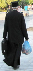 A Greek Orthodox priest carries his shopping home at The Cheshire Cat Blog