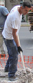 Athenian road worker repairing Athinas Street, Athens at The Cheshire Cat Blog