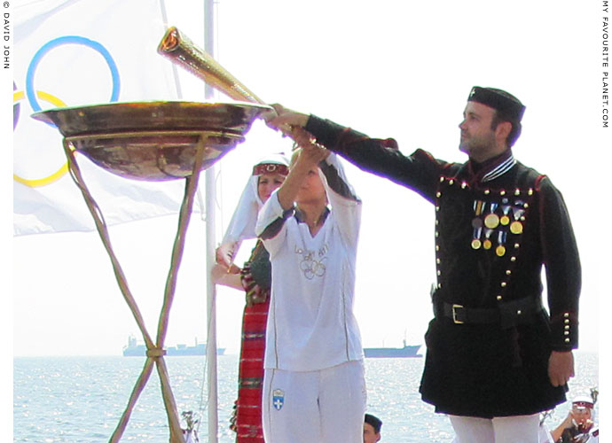 Greek torchbearer Giota Oikonomou lights the Olympic flame in the harbour of Thessalomiki, Macedonia, Greece at The Cheshire Cat Blog
