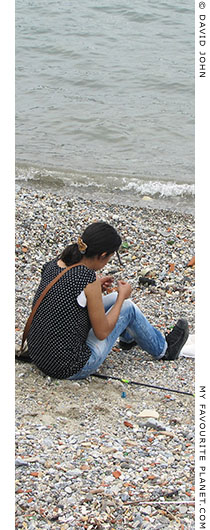 A young woman fishing on the town beach of Kusadasi, Turkey