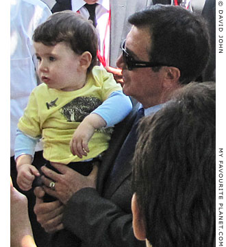 Rights and Equality Party leader Osman Pamuköglu holds a child in Selcuk, Turkey