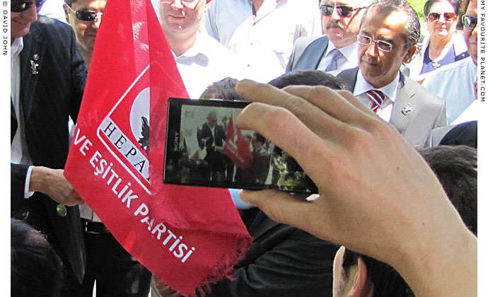 Rights and Equality Party member photographs the leader Osman Pamuköglu in Selcuk, Turkey at The Cheshire Cat Blog