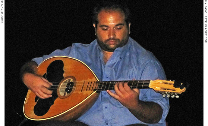 Bouzouki player playing traditional Cretan music in Pella, Greece at The Cheshire Cat Blog