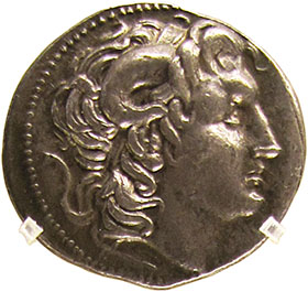 A silver tetradrachm coin depicting Alexander the Great wearing the ram's horns of Zeus Ammon.