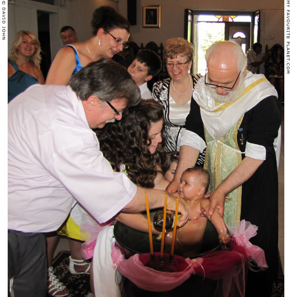 A baby is baptised in the village church, Koufovouno, Thrace, Greece at My Favourite Planet