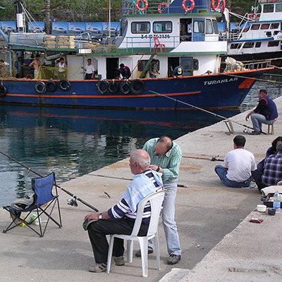 Angler having his hair cut on the causeway to Guvercin Ada (Pigeon Island), Kusadasi, Turkey at My Favourite Planet
