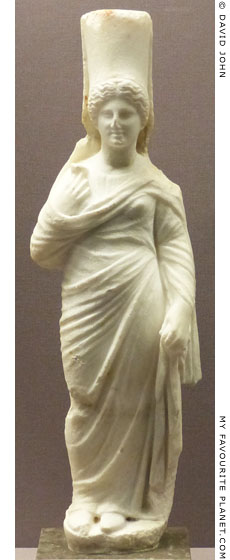 Marble statuette of Persephone wearing a high polos and holding a pomegranate flower at My Favourite Planet