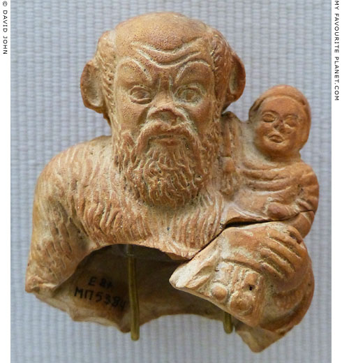 Terracotta figurine of Papposilenos holding the infant Dionysus in Piraeus at My Favourite Planet