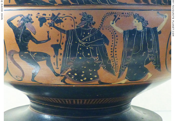 Dionysus standing between a satyr and a maenad playing krotala at My Favourite Planet