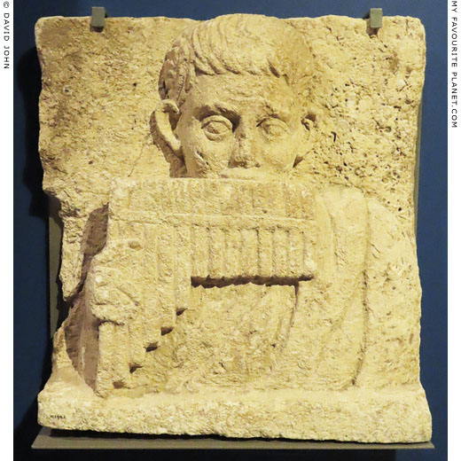 Limestone relief of a boy playing a syrinx rom Oxyrhynchus, Egypt at My Favourite Planet